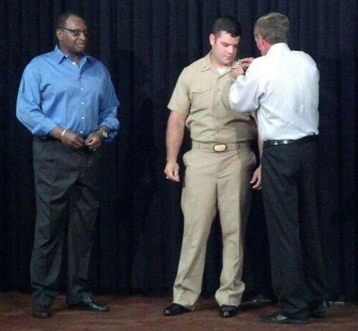Head coach Mike Shanahan pins two silver bars on the U.S. Navy uniform of Eric Kettani, a Redskins fullback, as part of a ceremony Tuesday at Redskins Park. Kettani was promoted to lieutenant. Running backs coach Bobby Turner (left) also pinned Kettani. (Rich Campbell / Washington Times)