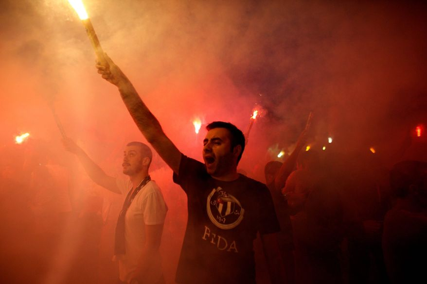 Protesters light flares and shout slogans during a protest at Taksim Square in Istanbul, on Tuesday. Thousands have joined anti-government rallies across since Friday, when police launched a pre-dawn raid against a sit-in protesting plans to uproot trees in the square. Since then, the demonstrations have spiraled into Turkey's biggest anti-government disturbances in years. (Associated Press)