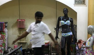 A man walks past a mannequin displaying lingerie at a mall in Mumbai on Friday, May 31, 2013. (AP Photo/Rajanish Kakade)