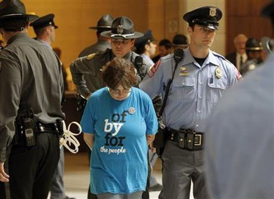 General Assembly Police and Raleigh Police escort a woman away after she was arrested at the Legislative Building as the Monday protests are held at the General Assembly in Raleigh, N.C. on Monday, June 3, 2013. (Associated Press)