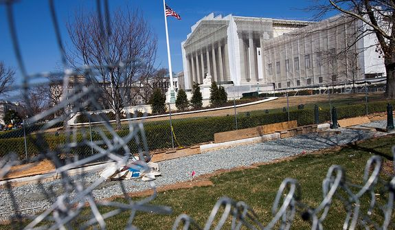 The Supreme Court is seen through fencing in Washington on Saturday March 23, 2013. (AP Photo/Jacquelyn Martin)