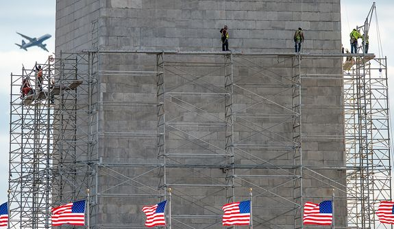 Workers begin building scaffolding around the Washington Monument to make repairs to stonework damaged in the 2011 earthquake,