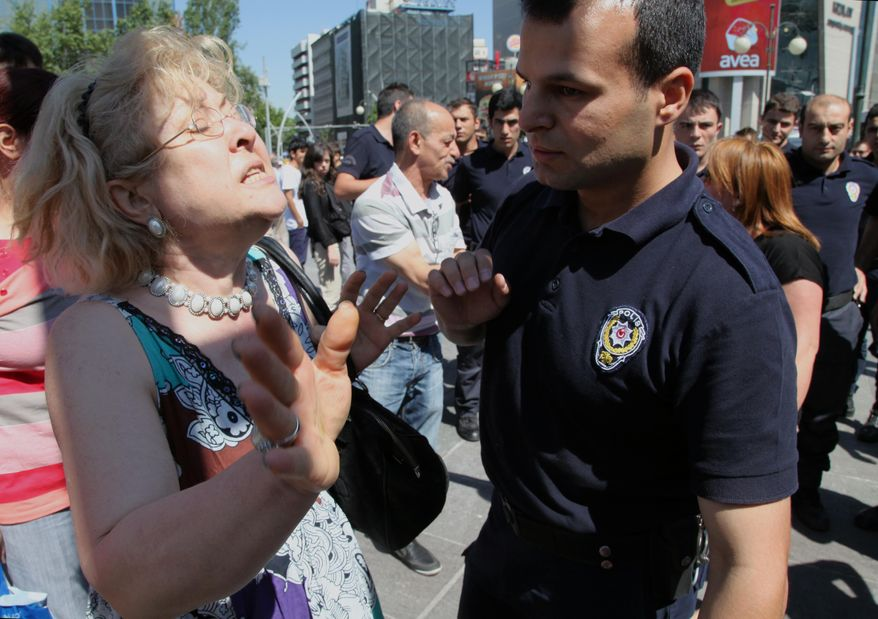 """A Turkish woman argues with riot police officers and ask them to not use tear gas against protesters, saying """"no more gas, please,"""" at the main Kizilay Square near the office of Turkish Prime Minister, Recep Tayyip Erdogan, in Ankara, Turkey, Tuesday, June 4, 2013. Protests, the biggest Turkey has seen in recent years, were sparked by a police crackdown of a peaceful sit-in to prevent the demolition of a park in Istanbul. (AP Photo/Burhan Ozbilici)"""