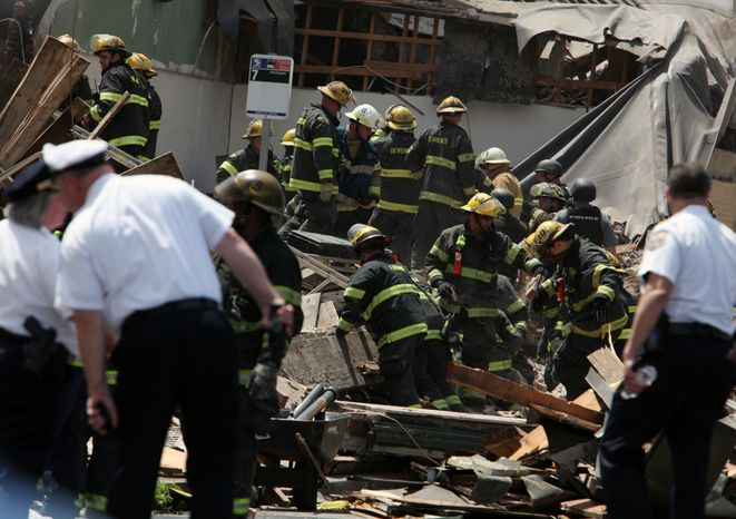 Rescue personnel search the scene of a four-story building collapse in downtown Philadelphia on Wednesday, June 5