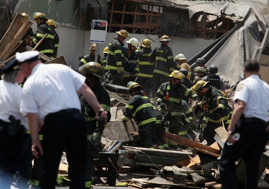 Rescue personnel search the scene of a four-story building collapse in downtown Philadelphia on Wednesday, June 5, 2013. The building was being demolished. (Associated Press)