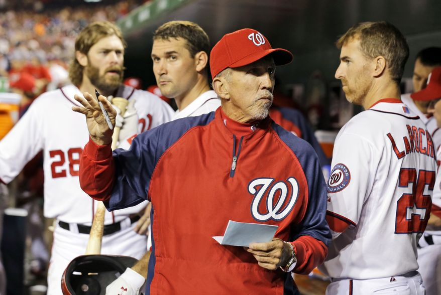 With Washington Nationals right fielder Jayson Werth (28), third baseman Ryan Zimmerman (11) and first baseman Adam LaRoche (25) behind him, manager Davey Johnson (5) checks the lineup, during a baseball game against the New York Mets at Nationals Park Tuesday, June 4, 2013, in Washington. The Nationals won 3-2. (AP Photo/Alex Brandon)