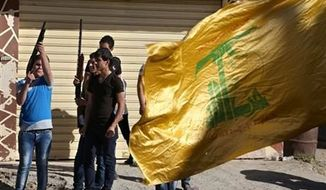 ** FILE ** Hezbollah supporters fire weapons as they celebrate the fall of the Syrian town of Qusair to forces loyal to President Bashar Assad and Hezbollah fighters, in Bazzalieh village, Lebanon, near the Lebanese-Syrian border, on Wednesday, June 5, 2013. (Associated Press)