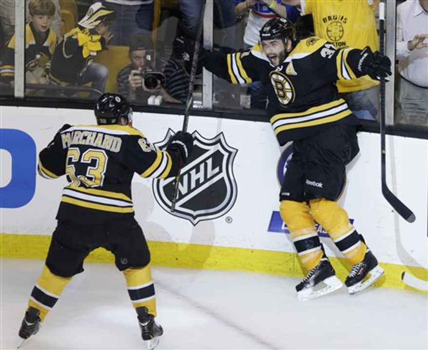 Boston Bruins center Patrice Bergeron (37) leaps as he celebrates his game-winning goal with teammate Brad Marchandd (63) against the Pittsburgh Penguins during the second overtime period in Game 3 of the NHL hockey Stanley Cup playoffs Eastern Conference finals, in Boston, early Thursday, June 6, 2013. The Bruins won 2-1, and take a 3-0 lead in the series. (AP Photo/Charles Krupa)