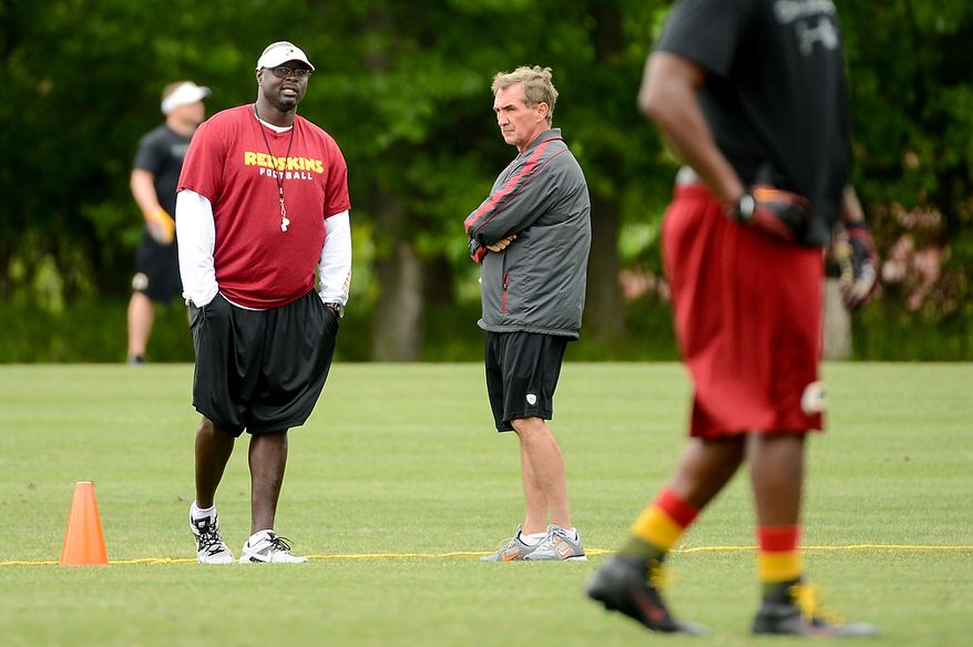 Washington Redskins head coach Mike Shanahan, center, talks with special teams coach Keith Burns, left, during a NFL football organized team activity at Redskins Park, Ashburn, Va., Thursday, June 6, 2013. (Andrew Harnik/The Washington Times)