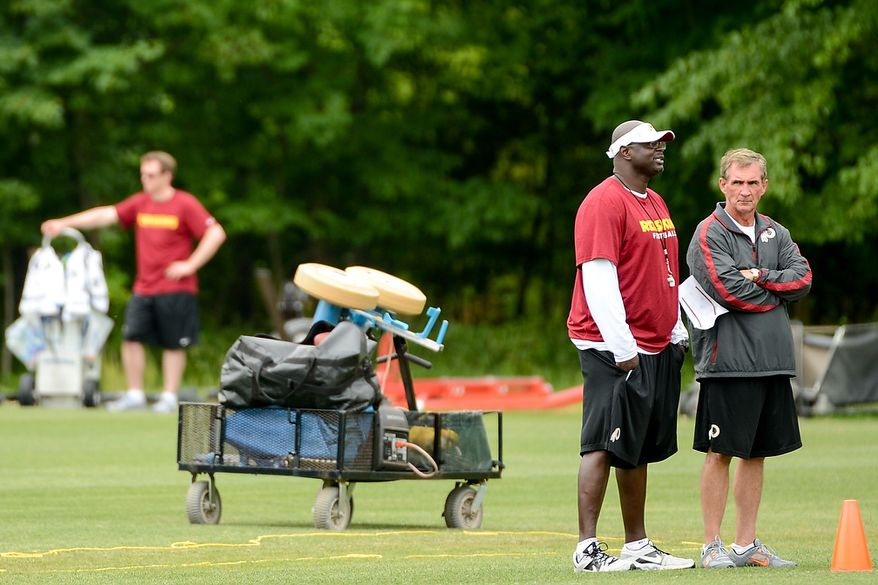 Washington Redskins head coach Mike Shanahan, right, talks with special teams coach Keith Burns, second from right, during a NFL football organized team activity at Redskins Park, Ashburn, Va., Thursday, June 6, 2013. (Andrew Harnik/The Washington Times)