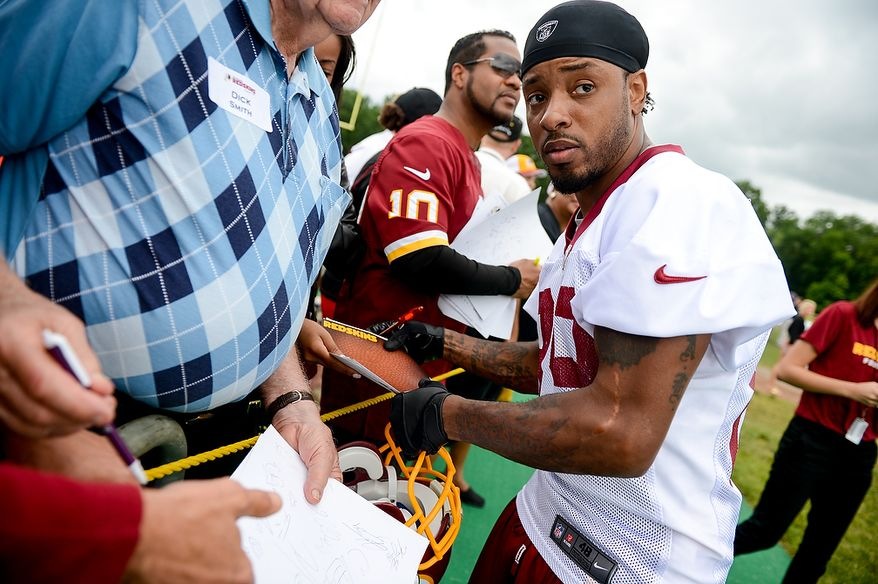 Washington Redskins wide receiver Santana Moss (89) signs autographs following a NFL football organized team activity at Redskins Park, Ashburn, Va., Thursday, June 6, 2013. (Andrew Harnik/The Washington Times)