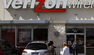 ** FILE ** In this Feb. 10, 2011 file photo, Chris Cioban, manager of the Verizon store in Beachwood, Ohio, holds up an Apple iPhone 4G. Britain's Guardian newspaper says the National Security Agency is currently collecting the telephone records of millions of U.S. customers of Verizon under a secret court order. (AP Photo/Amy Sancetta, File)