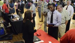 ** FILE ** In this photo taken Thursday, May 9, 2013, Jennifer Wilhoit of U.S. Express, left, talks with Devin Washington while others wait in line as 63 companies participate in a job fair at the Brainerd Crossroads in Chattanooga, Tenn. (AP Photo/Chattanooga Times Free Press, John Rawlston)