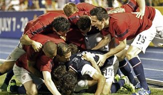 United States' bench players and Graham Zusi (19) pile up on top of teammate Brad Evans, obscured, to congratulate his for scoring the winning goal in the second half of the 2014 World Cup qualifying soccer match against Jamaica in Kingston, Jamaica, Friday, June 7, 2013. The US won 2-1. (AP Photo/Andres Leighton)