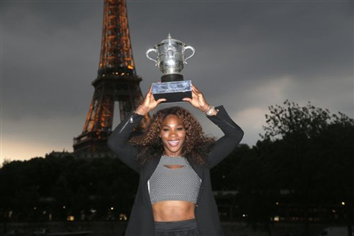 Serena Williams of the U.S. poses with her trophy after defeating Russia's Maria Sharapova in two sets 6-4, 6-4, in the women's final of the French Open tennis tournament, at Roland Garros stadium in Paris, Saturday June 8, 2013. The Eiffel Tower is seen background. (AP Photo/Christophe Ena)