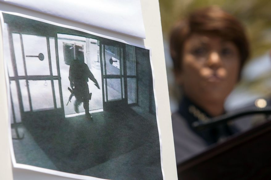 A picture of the shooting suspect entering the Santa Monica College library is seen as Chief Jacqueline Seabrook of the Santa Monica Police Department speaks during a news conference on Saturday June 8, 2013, in Santa Monica, Calif., to discuss the shootings that left five people dead, including the shooter, near the college Friday. (AP Photo/Ringo H.W. Chiu)