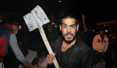 A Turkish protester holds a shovel as demonstrators prepare a barricade before clashing with riot police stationed on John F. Kennedy Street in front of the U. S. Embassy in Ankara, Turkey, the capital, on Sunday, June 9, 2013. (AP Photo/Burhan Ozbilici)