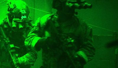 """This undated publicity photo released by Columbia Pictures Industries, Inc. shows Navy SEALs seen through the greenish glow of night vision goggles, as they prepare to breach a locked door in Osama Bin Laden's compound in Columbia Pictures' hyper-realistic new action thriller from director Kathryn Bigelow, """"Zero Dark Thirty."""" (AP Photo/Columbia Pictures Industries, Inc., Jonathan Olley)"""