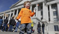 **FILE** Keaton Davidson, 2, holds his toy six-shooter gun during a rally for the 2nd Amendment at the capitol in Salt Lake City on March 2, 2013. (Associated Press)