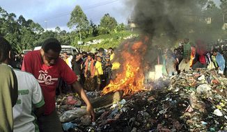 Hundreds of bystanders watch as Kepari Leniata, a woman accused of witchcraft, is burned alive in the Western Highlands provincial capital of Mount Hagen in Papua New Guinea on Wednesday, Feb. 6, 2013. (AP Photo/Post Courier)