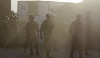 Afghan policemen guard after Taliban fighters attacked near Kabul's airport, Afghanistan, Monday, June 10, 2013. (AP Photo/Ahmad Jamshid)