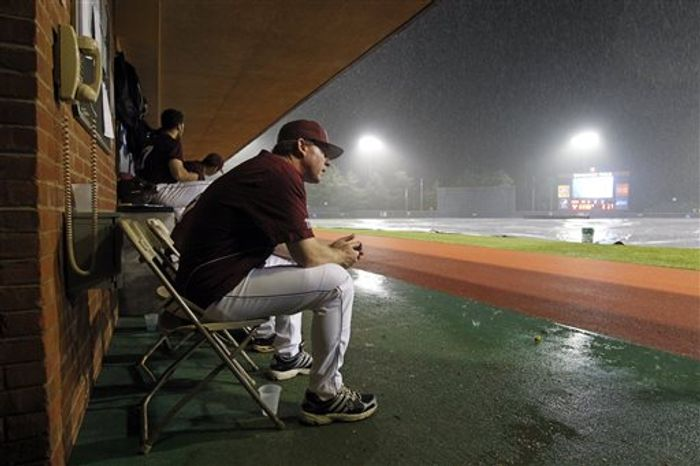 Mississippi State head coach John Cohen waits out a rain delay in the dugout during the seventh inning of the NCAA super regional college baseball game against Virginia in Charlottesville, Va., Sunday, June 9, 2013. (AP Photo/Andrew Shurtleff)