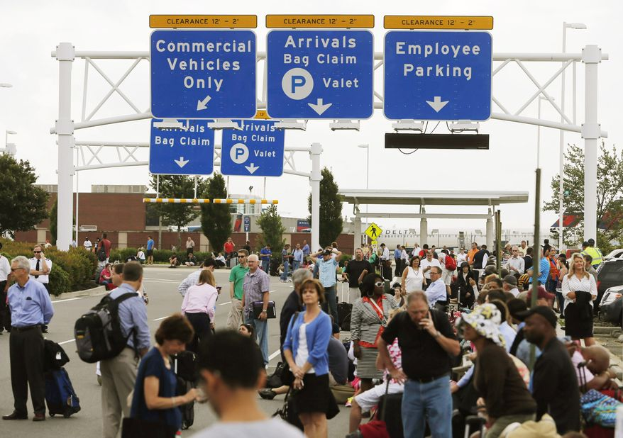 "Passengers line the vehicle ramp to the terminal at the Richmond International Airport after the building was evacuated at approximately 6:30 a.m. on Tuesday, June 11, 2013, in Richmond, Va. Authorities cleared the building after receiving what they called a ""credible threat."" Passengers and staff were allowed to return when the building was reopened after about a three-hour wait. (AP Photo/The Richmond Times-Dispatch, Joe Mahoney)"