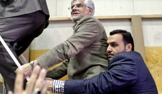 Escorted by his bodyguards, pro-reform Iranian presidential candidate Mohammad Reza Aref (center), a former vice president, arrives at his campaign rally in Tehran on June 10, 2013. The presidential election will be held on June 14. (Associated Press)