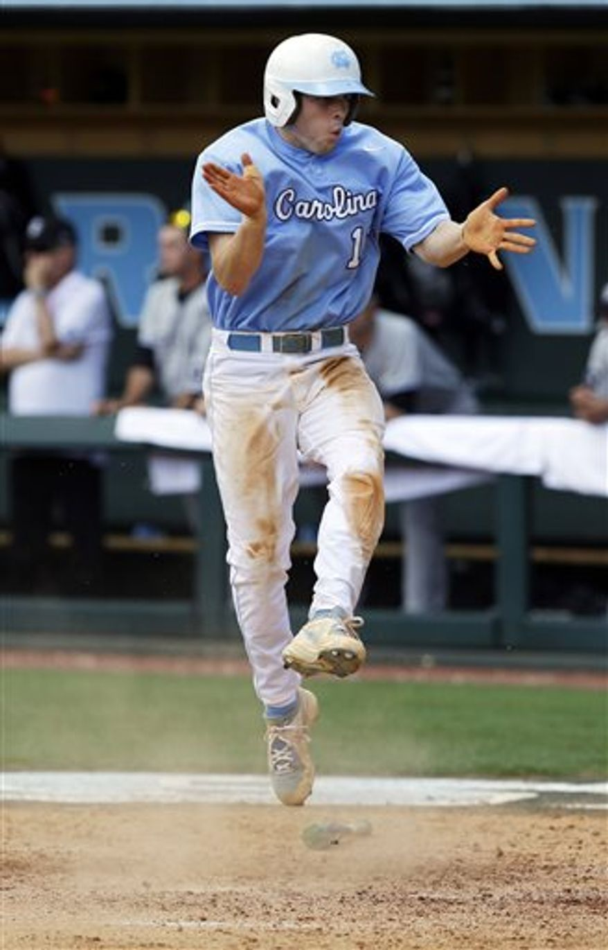 North Carolina's Landon Lassiter (12) reacts as he scores in the sixth inning of an NCAA college baseball tournament super regional game against South Carolina in Chapel Hill, N.C., Tuesday, June 11, 2013. North Carolina won 5-4 to advance to the College World Series. (AP Photo/Gerry Broome)