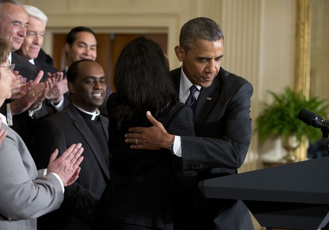 ** FILE ** President Obama hugs Tolu Olubunmi, an immigration activist, before speaking about immigration reform on June 11, 2013, in the East Room of the White Ho