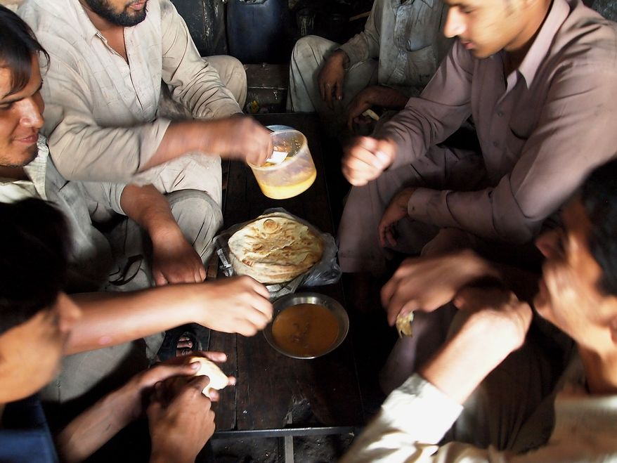 It's lunch time for the laborers at the truck art market in Rawalpindi. Inside the workshop they use a bench as a makeshift lunch table. They sit together and share the food they bring from home. (Azmat Ullah)