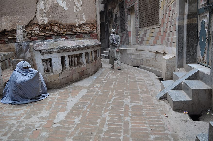 A woman sits on a street corner in the old city neighborhood in Peshawar, waiting for a passerby's attention. She does not have any other source of income and is forced to sit and beg. Photo / Ammad Ahmad Khan