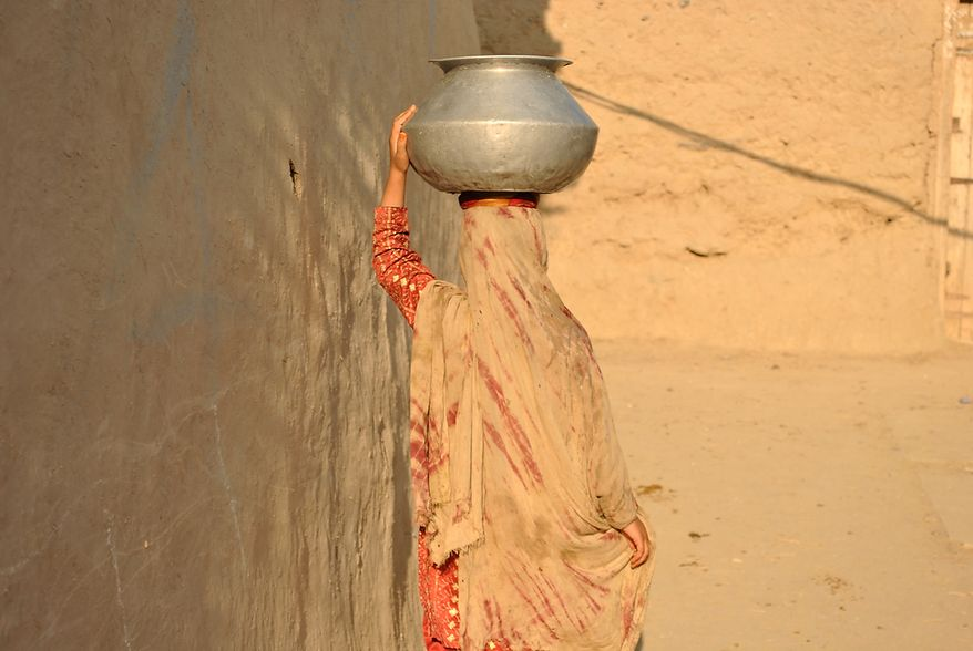 A woman returns home after fetching water in a village in Mohmand Agency (FATA). It is a woman's task to collect and carry water for domestic use. Village houses usually do not have a direct water supply. Photo / Alamgir Khan