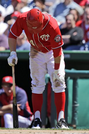 Bryce Harper, seen here grabbing his left knee, received PRP and cortisone injections in the knee on Monday. He will be reevaluated in one week. (Associated Press photo).