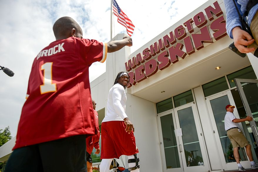 Lateef Brock, of Clinton, Md. who was visiting the Redskins with the Make a Wish foundation says goodbye to Washington Redskins quarterback Robert Griffin III (10), center, after practice during mini camp at Redskins Park, Ashburn, Md., Tuesday, June 11, 2013. (Andrew Harnik/The Washington Times)
