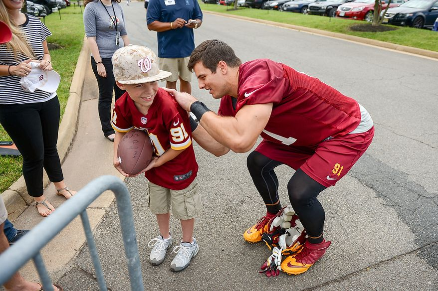 Washington Redskins outside linebacker Ryan Kerrigan (91) signs the shirt of Andrew Christopher, 9, of Fredericksburg, Md., at mini camp at Redskins Park, Ashburn, Md., Tuesday, June 11, 2013. (Andrew Harnik/The Washington Times)