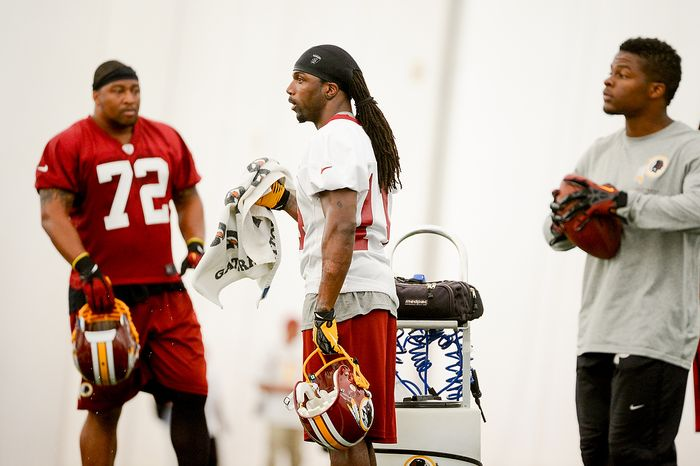 Wide receiver Donte Stallworth, center, rests between drills while trying out for the Washington Redskins during mini camp at Redskins Park, Ashburn, Md., Tuesday, June 11, 2013. (Andrew