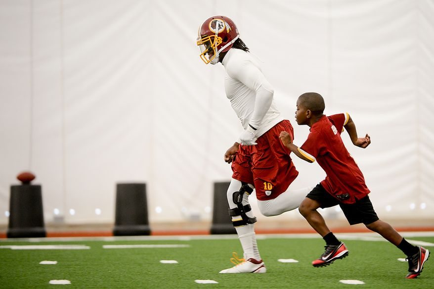 Washington Redskins quarterback Robert Griffin III (10) races Lateef Brock, of Clinton, Md., right, who was visiting the Redskins with the Make a Wish foundation during mini camp at Redskins Park, Ashburn, Md., Tuesday, June 11, 2013. (Andrew Harnik/The Washington Times)
