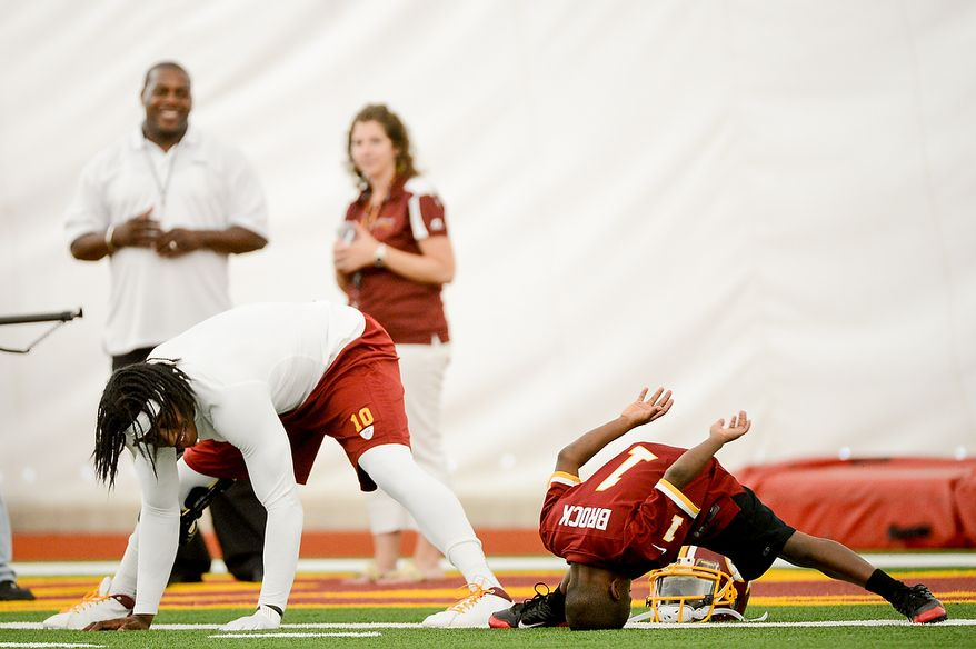 Washington Redskins quarterback Robert Griffin III (10) stretches with Lateef Brock, of Clinton, Md., right, who was  visiting the redskins with the Make a Wish foundation during mini camp at Redskins Park, Ashburn, Md., Tuesday, June 11, 2013. (Andrew Harnik/The Washington Times)