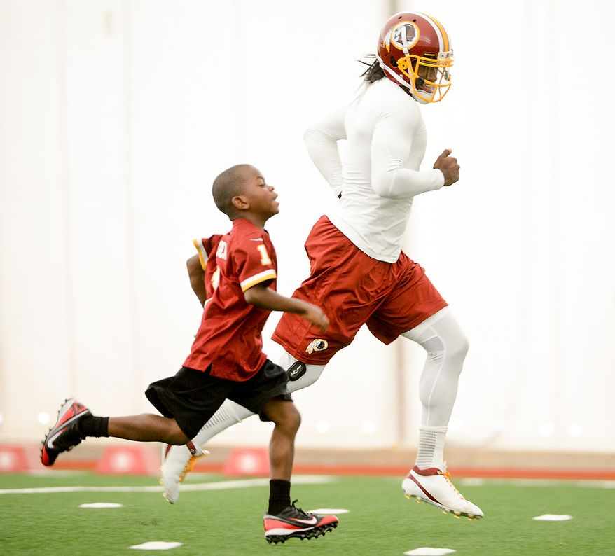 Washington Redskins quarterback Robert Griffin III (10) races Lateef Brock, of Clinton, Md., left, who was visiting the Redskins with the Make a Wish foundation during mini camp at Redskins Park, Ashburn, Md., Tuesday, June 11, 2013. (Andrew Harnik/The Washington Times)