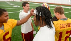 Washington Redskins offensive coordinator Kyle Shanahan, second from right, Washington Redskins quarterback Robert Griffin III (10), center, and the other quarterbacks come together at the conclusion of practice during mini camp at Redskins Park, Ashburn, Md., Tuesday, June 11, 2013. (Andrew Harnik/The Washington Times)