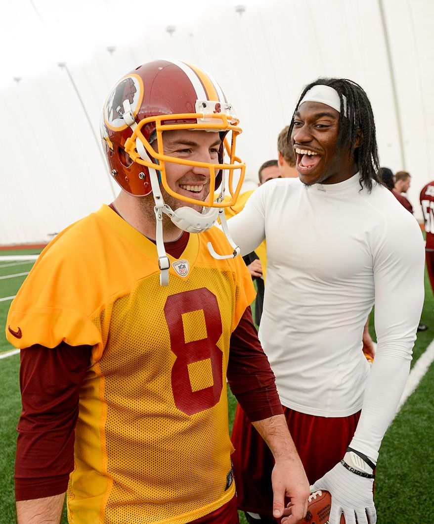 Washington Redskins quarterback Rex Grossman (8), left, and Washington Redskins quarterback Robert Griffin III (10) share a laugh together at the conclusion of practice during mini camp at Redskins Park, Ashburn, Md., Tuesday, June 11, 2013. (Andrew Harnik/The Washington Times)