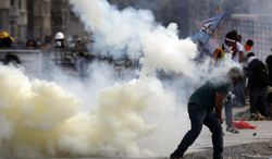 A protester throws back a tear gas canister during clashes in Taksim square in Istanbul, Tuesday, June 11, 2013. Hundreds of police in riot gear forced through barricades in Istanbul's central Taksim Square early Tuesday, pushing many of the protesters who had occupied the square for more than a week into a nearby park. (AP Photo/Kostas Tsironis)