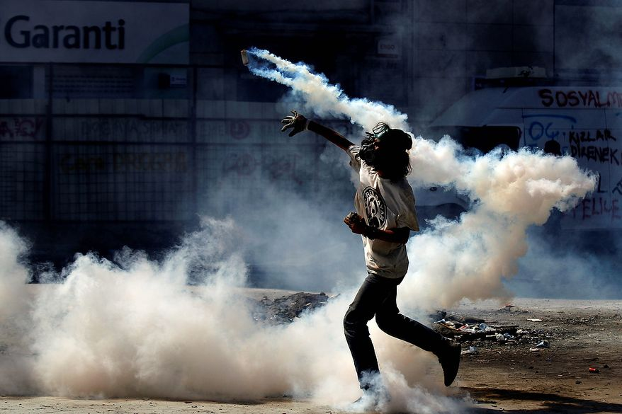 A protester throws a tear gas canister back to police during clashes in Taksim Square in Istanbul on Tuesday, June 11, 2013. Hundreds of police in riot gear forced through barricades and pushed many of the protesters who had occupied the square for more than a week into a nearby park. (AP Photo/Kostas Tsironis)