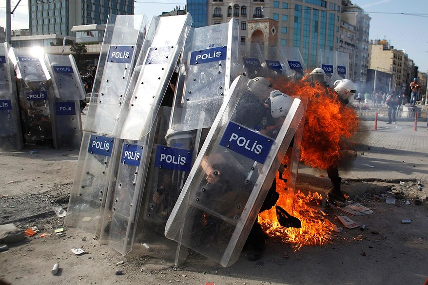 A gasoline bomb explodes in front of riot policemen during clashes in Taksim Square in Istanbul on Tuesday, June 11, 2013. Hundreds of police in riot gear forced through barricades and pushed many of the protesters who had occupied the square for more than a week into a nearby park. (AP Photo/Kostas Tsironis)