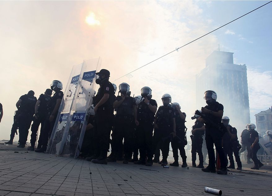 Police stand amid tear gas during clashes with protesters in Taksim Square in Istanbul on Tuesday, June 11, 2013. Hundreds of police in riot gear forced through barricades and pushed many of the protesters who had occupied the square for more than a week into a nearby park. (AP Photo/Thanassis Stavrakis)