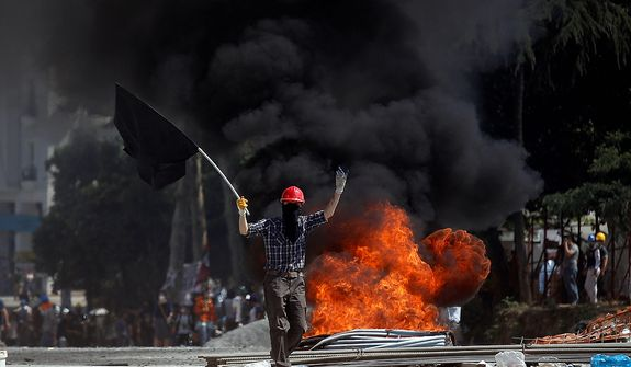 A protester gestures to riot police as he walks in front of a burning barricade during clashes in Taksim Square in Istanbul on Tuesday, June 11, 2013. Hundreds of police in riot gear forced through barricades and pushed many of the protesters who had occupied the square for more than a week into a nearby park. (AP Photo/Kostas Tsironis)