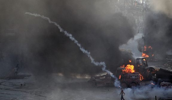 A protester throws tear gas at police as a bulldozer blazes during clashes in Taksim Square in Istanbul on Tuesday, June 11, 2013. Hundreds of riot police overran improvised barricades on the central square and fired tear gas, rubber bullets and water cannon in running battles with protesters who have been occupying the area for more than a week. (AP Photo/Thanassis Stavrakis)
