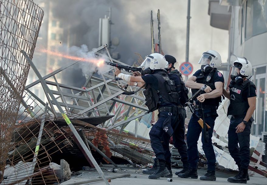 Turkish riot police fire tear gas during clashes in Taksim Square in Istanbul on Tuesday, June 11, 2013. Hundreds of police in riot gear forced through barricades and pushed many of the protesters who had occupied the square for more than a week into a nearby park. (AP Photo/Vadim Ghirda)