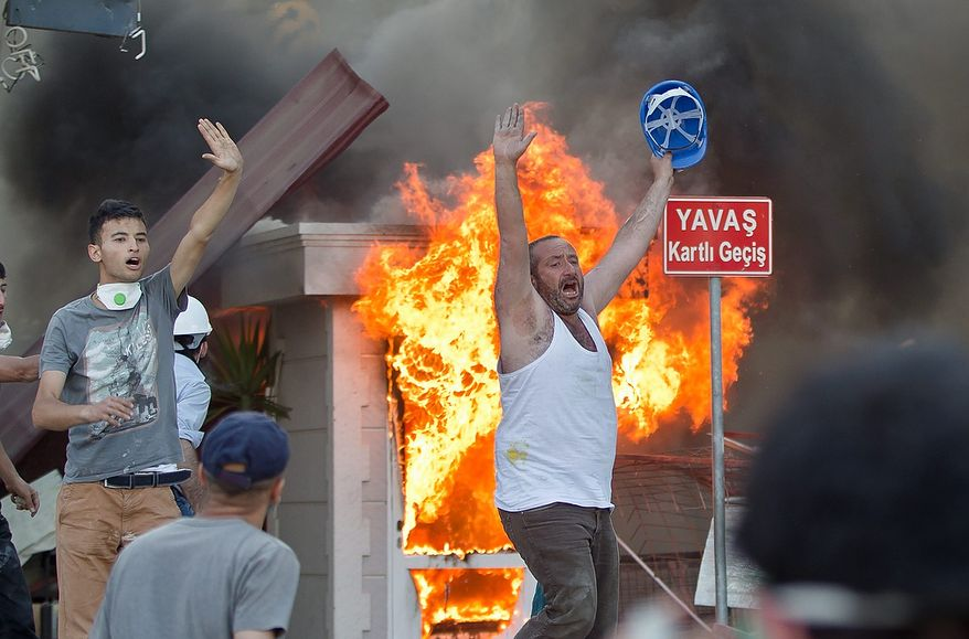 Protesters react during clashes in Taksim Square in Istanbul on Tuesday, June 11, 2013. Hundreds of police in riot gear forced through barricades and pushed many of the protesters who had occupied the square for more than a week into a nearby park. (AP Photo/Vadim Ghirda)